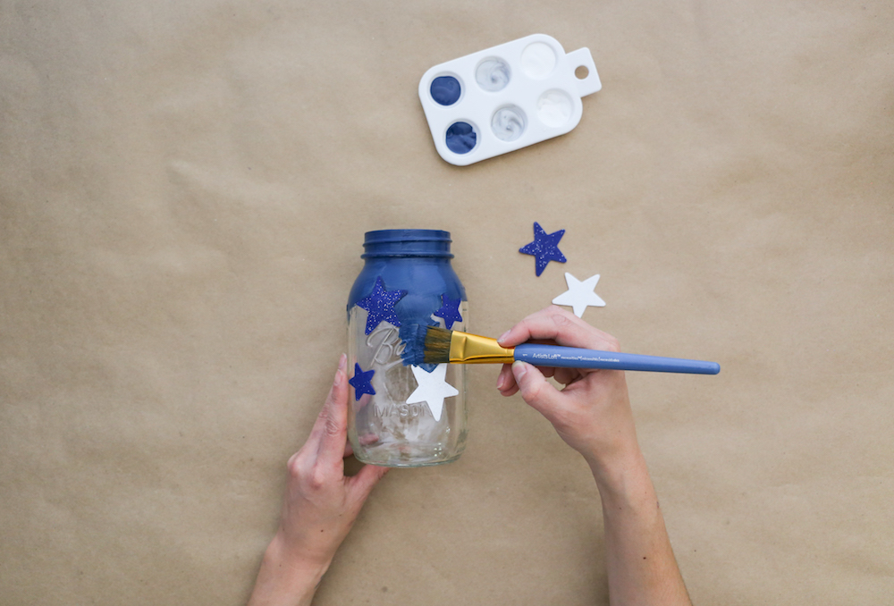 Painting jar with blue paint over stars