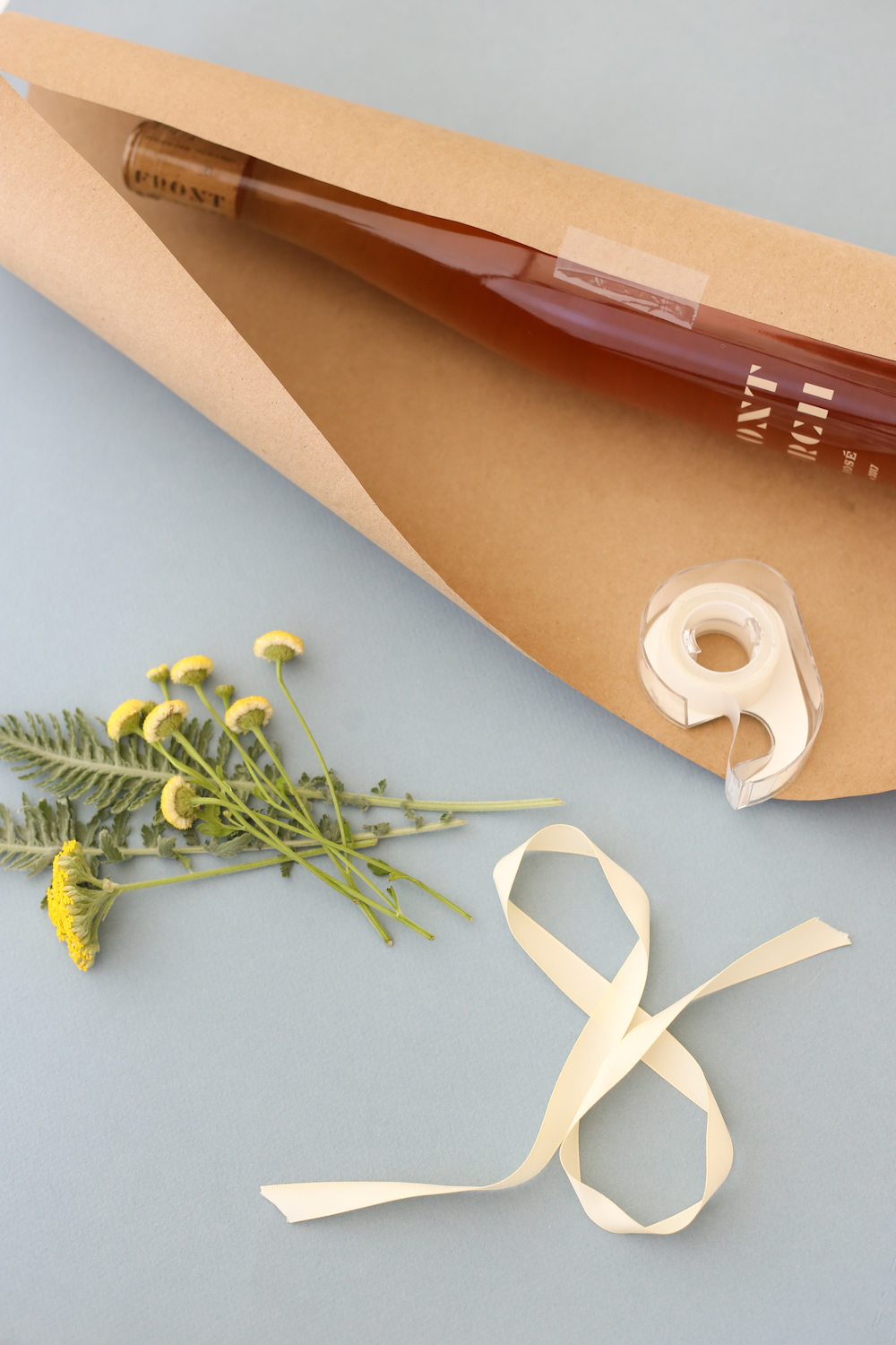 Wine bottle in craft paper with tape, flowers, and ribbon