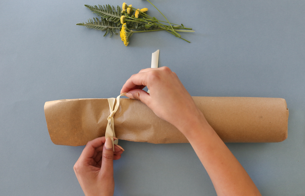Craft paper being tied with ribbon